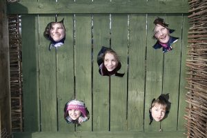 Bosworth fence - faces peering through holes in the wooden fence